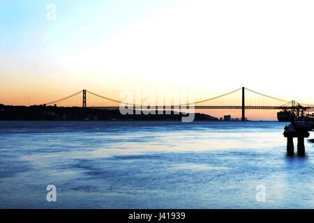 Coucher de soleil sur le Tage et le pont suspendu du 25 avril. Banque D'Images