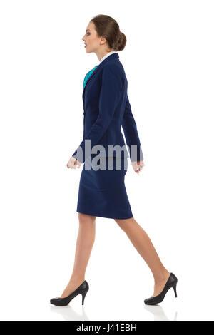 Jeune femme en costume bleu, jupe et talons hauts noir marche à pied. Vue de côté. Studio pleine longueur shot isolé Banque D'Images