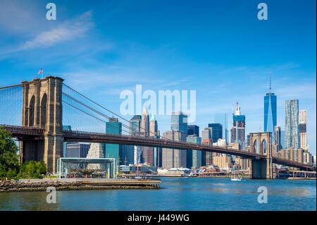 Vue panoramique lumineux de jour le pont de Brooklyn avec le Lower Manhattan skyline à travers l'East River sous Banque D'Images
