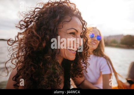 Close up shot of young woman outdoors with female friend en arrière-plan. Banque D'Images