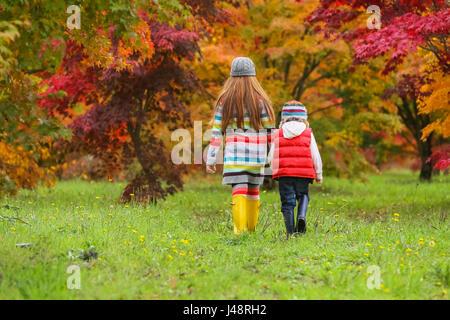 Un jeune garçon et fille portant des bottes en caoutchouc et des vêtements colorés à pied à travers un champ vers Banque D'Images