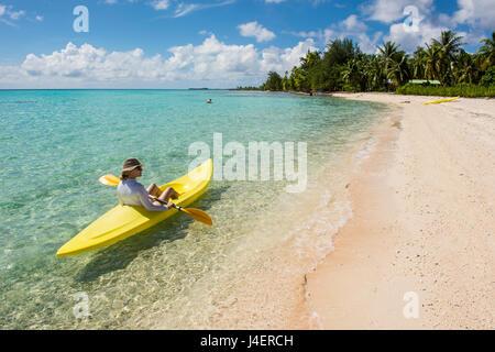 Femme kayak dans les eaux turquoises de Tikehau, Tuamotu, Polynésie Française, Pacifique