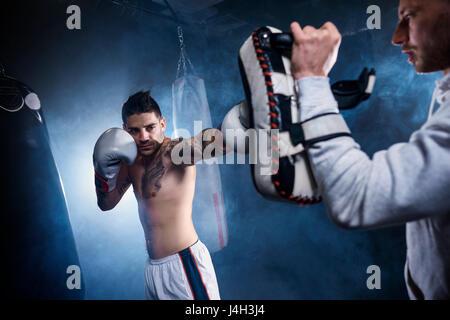 Close up de boxer avec formation coach exigeant Banque D'Images