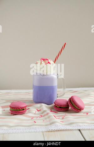 Café pourpre en pot Mason Tasse stylisée avec ses macarons et une décoration colorée. Lait frappé aux bleuets. Café Banque D'Images