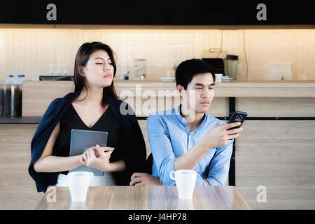 Jeune couple amateur asiatique using smartphones au café. Petite amie jalouse peeking pour espionner le téléphone Banque D'Images