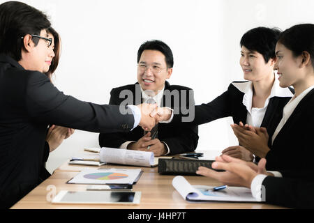 Asian businessman and businesswoman shaking hands in conference room. Business people shaking hands concept accord. Banque D'Images