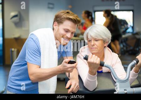 Entraîneur personnel montrant chronomètre temps de senior client Banque D'Images