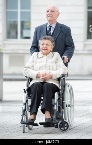 Hauts homme pousse sa mobilité épouse par la ville Banque D'Images
