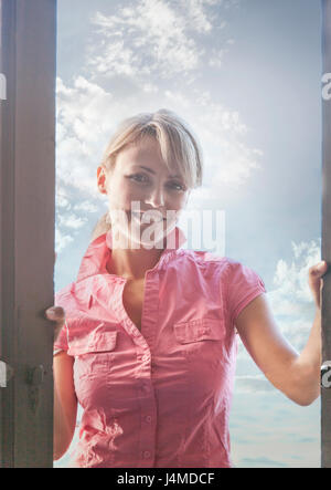 Portrait of smiling Caucasian woman standing in doorway Banque D'Images