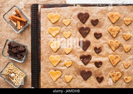 Les cookies en forme de coeur sur une tôle à biscuits ingrédients près de Banque D'Images