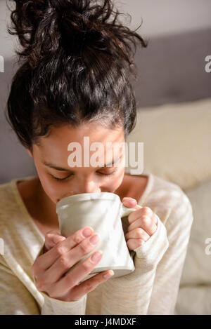 Hispanic woman drinking coffee Banque D'Images