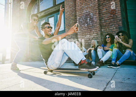 Ami Woman sitting on skateboard en ville Banque D'Images