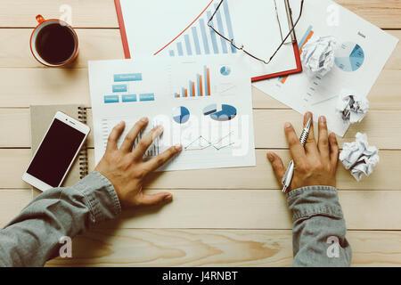 Vue supérieure de la personne d'affaires de discuter sur les tableaux et graphiques de l'ordinateur portable aussi,Black,café,fixes,stylo Banque D'Images