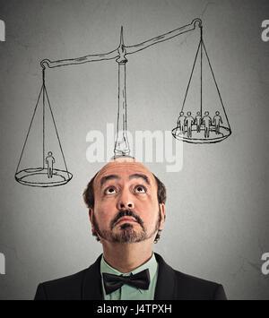 Businessman avec l'échelle au-dessus de la tête un homme pesant plus de gens d'affaires hors groupe sur un équilibre. Banque D'Images