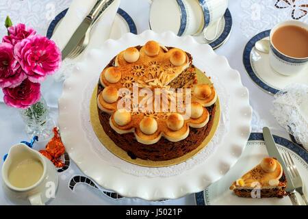 Simnel cake - gâteau aux fruits traditionnel de Pâques décorés de massepain sur un set de table pour le thé. Banque D'Images