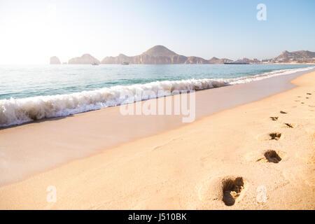 Vagues se brisant sur le rivage sur la plage de Cabo San Lucas, los Arcos avec en arrière-plan. Banque D'Images