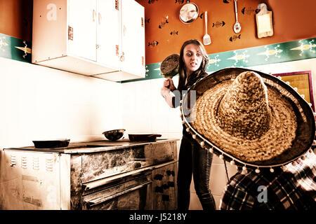 Jeune femme en colère brandissant une poêle à un homme en sombrero debout près de old dirty plaque avec utilisé Banque D'Images