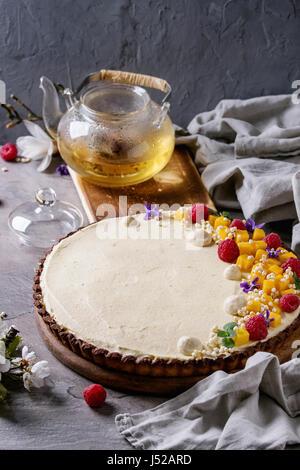 Tartelette au chocolat maison décorée par la mangue, framboises, menthe, riz soufflé et fleurs comestibles servi Banque D'Images