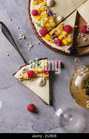 Des tranches de tarte au chocolat et un morceau de tarte décoré par la mangue, framboises, menthe, riz soufflé et Banque D'Images