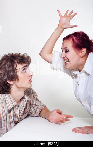 Une jeune femme en colère brandissant son mari sur un fond clair Banque D'Images
