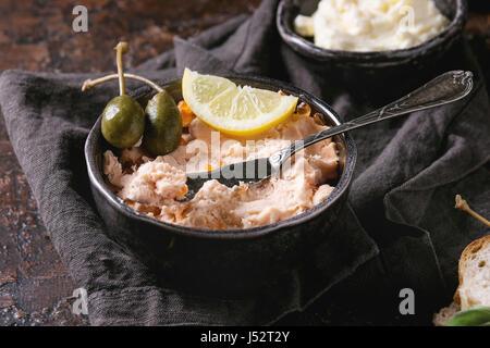 Black bol de pate de saumon avec du caviar rouge servi avec du beurre, des tranches de pain, les câpres, les herbes Banque D'Images