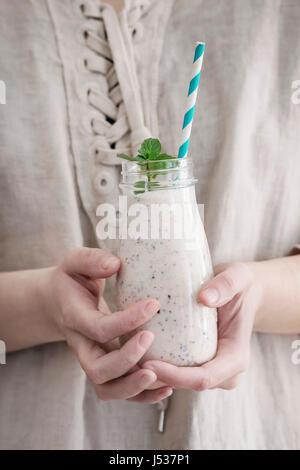 Bouteille de smoothie with chia seeds, les bleuets, les feuilles de menthe et rayé rétro tube cocktail de femmes. Banque D'Images