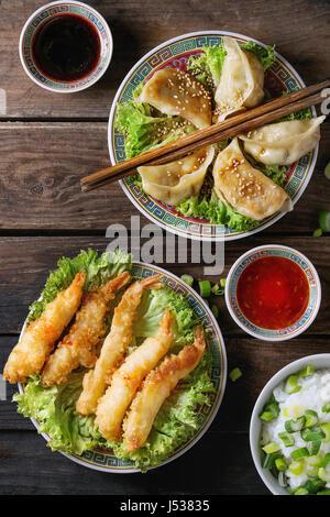 Poêlée de Crevettes tempura et les gyozas potstickers sur laitue salade avec les sauces et le riz. Servi dans la Banque D'Images