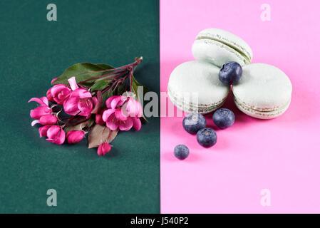 Fleurs roses à côté de macarons à la myrtille Banque D'Images