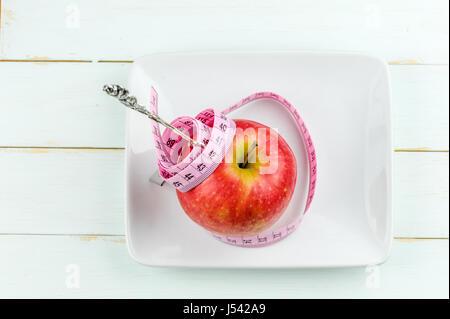 Pomme rouge avec un ruban à mesurer et la fourche sur fond de bois, l'alimentation concept Banque D'Images