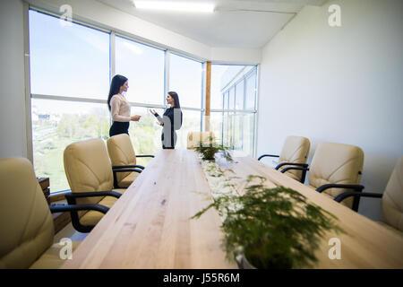 Deux businesswomen talking dans un bureau avec réflexion montrant sur la paroi en verre à côté d'eux Banque D'Images
