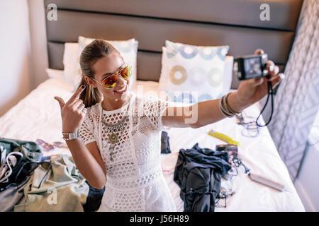 Diffusion d'enregistrement vlogger femelle avec un appareil photo numérique. Une femme qui l'affichage vidéo selfies vêtements mode et bijoux.