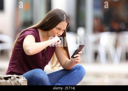 Femme en colère mauvaise réception de contenus en ligne dans un téléphone mobile assis dans un banc dans la rue Banque D'Images