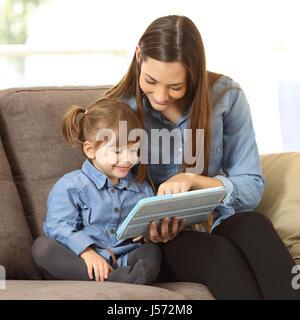 Mère montrant le contenu des médias en ligne pour ses deux années la fille dans un comprimé assis sur un canapé Banque D'Images