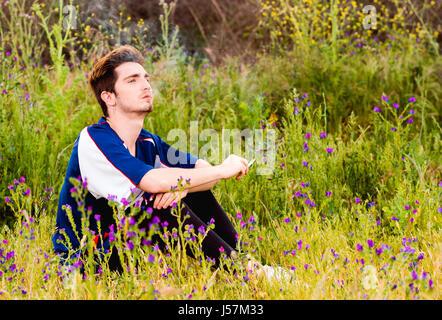 Homme seul fume une cigarette dans un champ