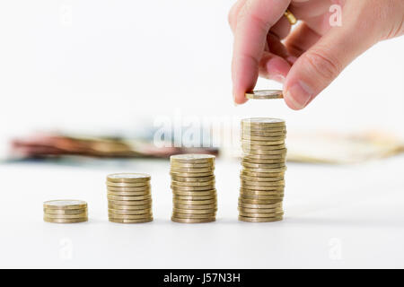 Image main de femme libre de l'un d'empilage des pièces en euros dans l'augmentation de colonnes sur fond blanc Banque D'Images