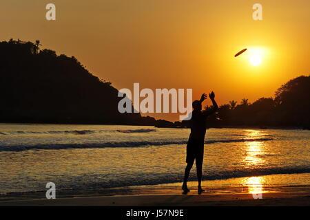 Homme jouant sur Frisbee plage de Palolem, Sud de l'Inde, Goa, Anjuna, Arambol, d'Agonda,Cola côté mer au coucher Banque D'Images