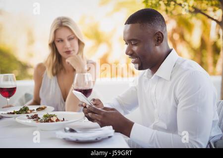L'homme ignorant bored femme lors de l'utilisation de téléphone mobile en restaurant Banque D'Images