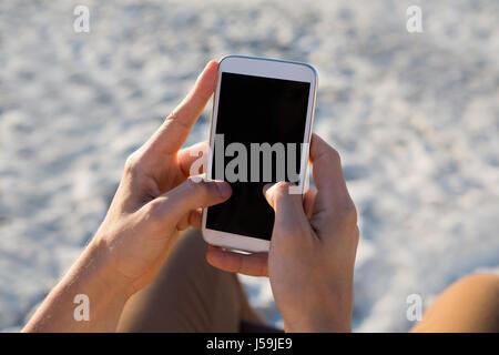 Portrait de l'homme à l'aide de mains mobile phone at beach Banque D'Images
