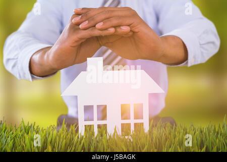 Maison blanche protégé par un homme dans l'arrière-plan sur les arbres en paysage herbeux Banque D'Images