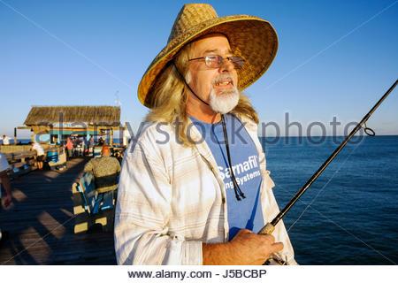 Floride Cocoa Beach Cocoa Beach Pier Atlantic Ocean Man chapeau de paille de canne à pêche pêcheur longs cheveux Banque D'Images