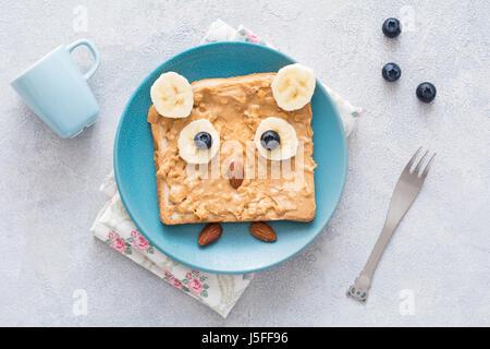 Le beurre d'arachide rôtie pour jeunes en forme de funny cute owl sur une plaque bleue. Vue d'en haut Banque D'Images