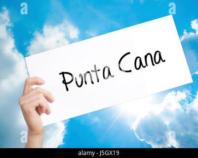Punta Cana signer sur papier blanc. Tenir la main de l'homme papier avec texte. Isolé sur fond de ciel. Concept Banque D'Images