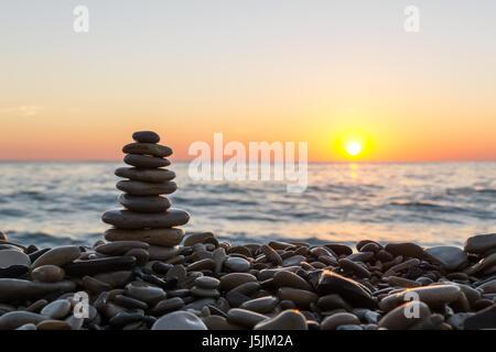 Pierres empilées sur la plage de galets sur le coucher du soleil. Banque D'Images