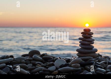 Cairn de pierres empilées avec soleil sur la plage de galets sur le coucher du soleil. Banque D'Images