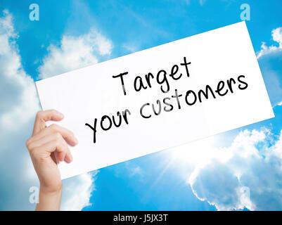 Vos clients cible signer sur papier blanc. Tenir la main de l'homme papier avec texte. Isolé sur fond de ciel. Concept Banque D'Images