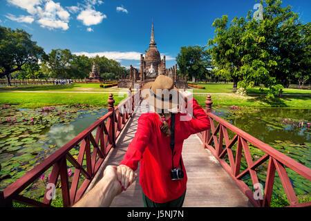 Woman in red shirt touristiques tenant son mari par la main et aller à l'ancien stupa dans Sukhohai Historical Park, Banque D'Images