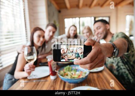 Groupe d'amis en train de dîner et prendre des selfies smartphone à la table Banque D'Images