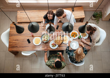 Vue de dessus du groupe de personnes qui, tout en s'asseyant à la table en bois rustique à la maison Banque D'Images