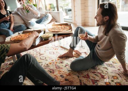 Jeune homme attrayant détendue boire du vin et de manger une pizza avec des amis à la maison Banque D'Images