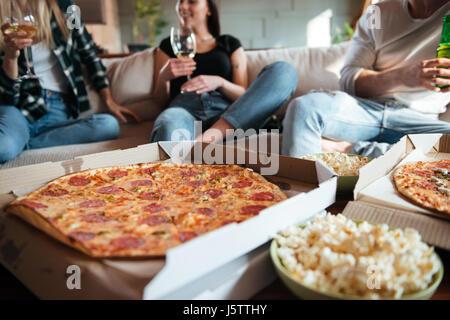 Groupe de professionnels jeunes eating pizza, boire du vin et de la bière sur le canapé à la maison Banque D'Images